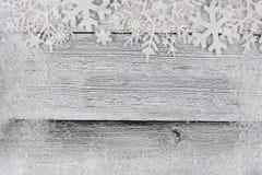 Weihnachtsschneeflocken-Spitzengrenze mit Schneerahmen auf weißem Holz Stockfotos