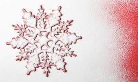 Weihnachtsschneeflockenform auf dem Schnee mit rotem Hintergrund Lizenzfreies Stockbild