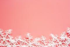 Weihnachtsschneeflockenverzierungen und -dekoration auf rosa Hintergrund stockfotografie