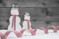 Weihnachtsschneemänner mit Schnee und Band auf grauem hölzernem Hintergrund Stockbilder