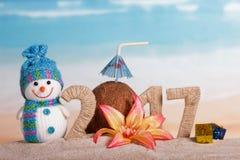 Weihnachtsschneemann, Kokosnuss und Aufschrift 2017 im Sand, verziert mit Blume, Geschenke Lizenzfreies Stockfoto