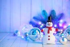 Weihnachtsschneemann mit Bällen und Girlande auf hölzernem Brett Lizenzfreie Stockbilder