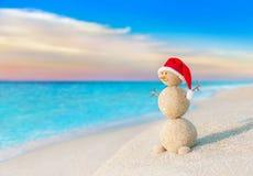Weihnachtsschneemann in rotem Sankt-Hut am Sonnenuntergangseestrand Lizenzfreies Stockfoto