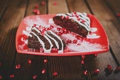 Weihnachtsschokoladenkuchennachtisch mit Granatapfel auf hölzernem tabl Stockbild