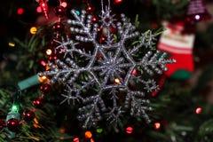 Weihnachtssilberne Schneeflockenverzierung, die im Baum hängt Stockbild