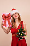 Weihnachtssinnliches blondes Mädchen mit Geschenkbox und Baum Stockbilder