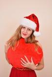 Weihnachtssinnliches Mädchen mit einem großen Herzgeschenk, in Sankt-Kostüm Stockfoto