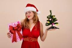 Weihnachtssinnliches Mädchen mit Geschenkbox und Baum, in Sonta-Kostüm Stockfotografie