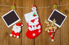 Weihnachtssocke für Geschenke und ein leerer Bilderrahmen auf einem hölzernen Stockbild