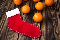 Weihnachtssocke und -mandarinen auf hölzernem Brett Stockfotos