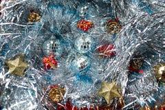 Weihnachtsspielwaren auf dem silbernen Lametta Stockfotos