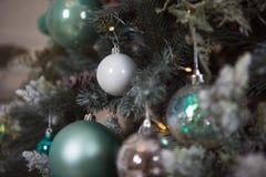 Weihnachtsspielwaren auf einem grünen künstlichen Weihnachtsbaum in einer leichten Art und in den Goldlichtgirlanden lizenzfreie stockfotos