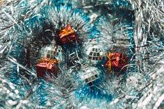 Weihnachtsspielwaren auf silbernem Lametta Lizenzfreie Stockfotos