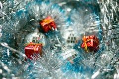 Weihnachtsspielwaren auf silbernem Lametta Stockbilder