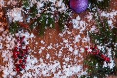 Weihnachtsspielwaren, Beeren und gezierte Zweige auf einem hölzernen Hintergrund schnee Lizenzfreies Stockfoto