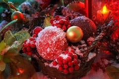 Weihnachtsspielwaren in einem Weidenkorb werden mit Schnee angesichts einer roten Laterne bedeckt Lizenzfreies Stockfoto