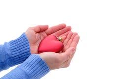 Weihnachtsspielzeug in Form eines Herzens in seinen Händen Stockbilder