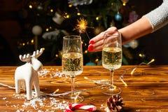 Weihnachtsspielzeug-Rotwilddekorationen auf dem Tisch mit Champagner Lizenzfreie Stockbilder