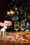 Weihnachtsspielzeug-Rotwilddekorationen auf dem Tisch mit Champagner Stockfoto