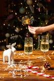 Weihnachtsspielzeug-Rotwilddekorationen auf dem Tisch mit Champagner Stockfotografie