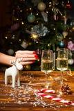 Weihnachtsspielzeug-Rotwilddekorationen auf dem Tisch mit Champagner Lizenzfreie Stockfotos