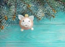 Weihnachtsspielzeug-Schweinkarte auf einem hölzernen Hintergrund, Schnee, Baumast stockfoto