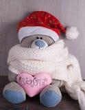 Weihnachtsspielzeugbär mit Sankt-Hut auf hölzernem Hintergrund Lizenzfreies Stockfoto