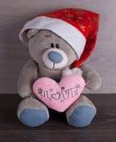 Weihnachtsspielzeugbär mit Sankt-Hut auf hölzernem Hintergrund Stockbilder