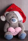 Weihnachtsspielzeugbär mit Sankt-Hut auf hölzernem Hintergrund Stockbild