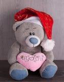Weihnachtsspielzeugbär mit Sankt-Hut auf hölzernem Hintergrund Stockfoto