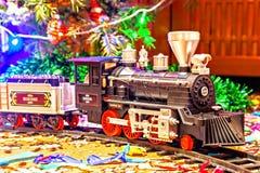 Weihnachtsspielzeugeisenbahn nahe einem Weihnachtsbaum mit Lichtern Stockbild