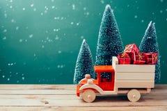 Weihnachtsspielzeuglastwagen mit Geschenkboxen und Kiefer auf Holztisch über grünem Hintergrund Lizenzfreies Stockfoto