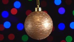 Weihnachtsspinnt goldenes glänzendes Ballspielzeug Nahaufnahme Dekor mit den funkelnden Baumlichtern des neuen Jahres stock video footage