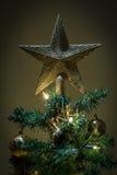 Weihnachtsstern auf Baum mit den gelben und grünen Kugeln Stockfotografie