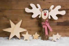 Weihnachtssterne und -elche mit Schnee auf hölzernem Hintergrund Lizenzfreies Stockfoto