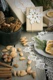 Weihnachtsstillleben mit Geschenk, Mandel, Zimt, Schneeflocken auf Holztisch Lizenzfreie Stockfotos