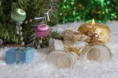Weihnachtsstillleben mit Kerze, Glocken, Geschenk und Grün hebt im Hintergrund hervor Stockbilder