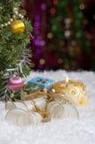Weihnachtsstillleben mit Kerze, Glocken, Geschenk und Höhepunkten im Hintergrund Stockbilder