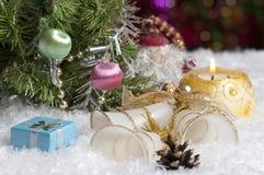 Weihnachtsstillleben mit Kerze, Glocken, Geschenk und Kegel Stockbilder