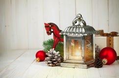Weihnachtsstillleben mit Lampenbällen und -geschenk auf hölzernem Brett Stockfotografie
