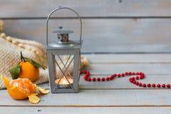 Weihnachtsstillleben mit Laterne, Plaid, Tangerine und rotem bea Stockbild