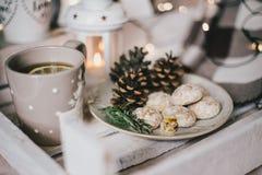 Weihnachtsstillleben mit Tee, Lichtern, Kegeln und Plätzchen Lizenzfreie Stockfotos