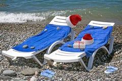 Weihnachtsstrand: ein Klappstuhl, ein Baum und ein Hut von Santa Claus 3 d-Sichtbarmachung Stockbild