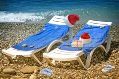 Weihnachtsstrand: ein Klappstuhl, ein Baum und ein Hut von Santa Claus 3 d-Sichtbarmachung Lizenzfreies Stockfoto