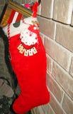 Weihnachtsstrumpf gefüllt mit Geschenken Stockfotografie