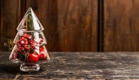 Weihnachtssymbolbaum vom Glas mit Dekoration auf rustikaler Tabelle über hölzernem Hintergrund Lizenzfreie Stockfotografie