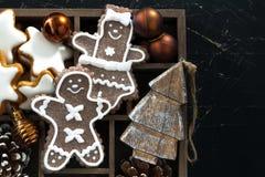 Weihnachtssymbole in einer Holzkiste auf schwarzem hölzernem Hintergrund Lizenzfreies Stockfoto