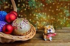 Weihnachtssymbolhund, Weihnachtsdekorationen auf einem hölzernen backgrou Lizenzfreies Stockbild