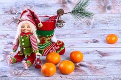 Weihnachtsszene mit Elfe, Weihnachtssocken, Tangerinen und Fichte Lizenzfreie Stockfotografie
