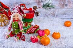 Weihnachtsszene mit Elfe, Weihnachtssocken, Tangerinen und Geschenken Lizenzfreie Stockfotografie